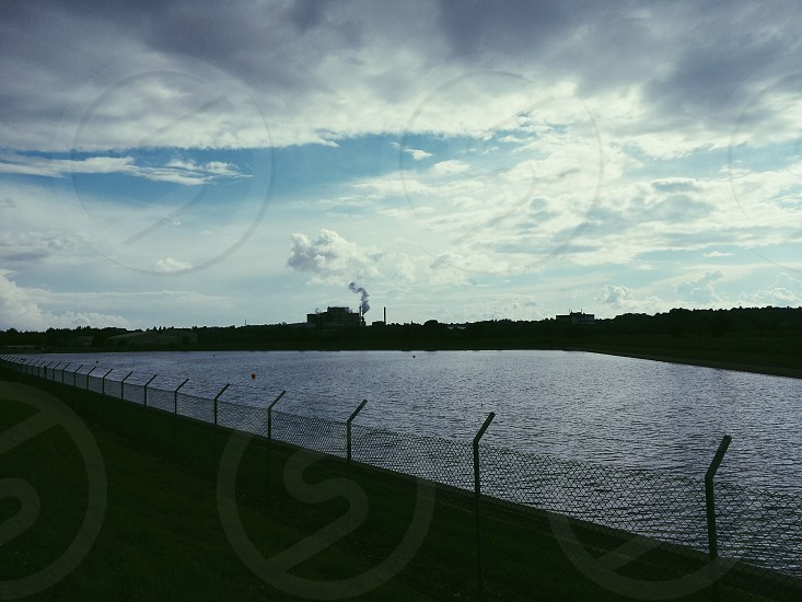 factory with blue sky and clouds and the view of a large lake / reservoir  photo