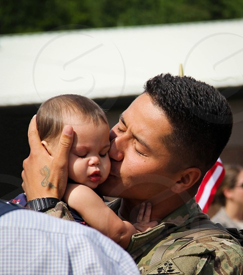 I went to Afghanistan last year. I deployed with this soldier. Two months after we were there his wife called him and said she was pregnant with twins! As I got off the plane instead of going to see my family I haven't seen for a year I pulled out my camera and caught the moment he met one of his twin daughters for the first time! An incredible emotional moment!  photo