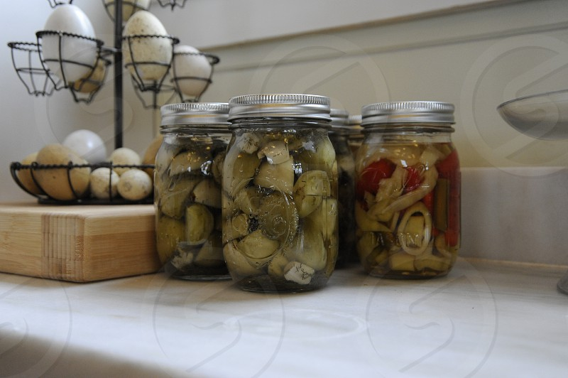 Jars of pickles on counter with eggs in holder photo