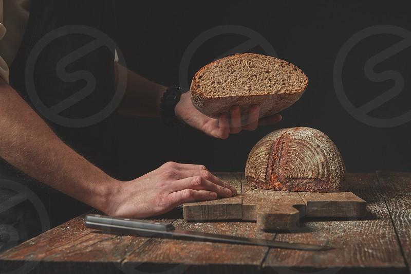 Baker keeps half freshly baked organic bread on a dark background photo