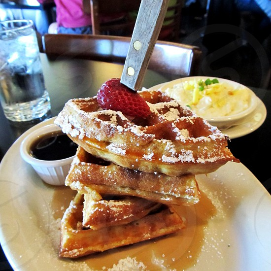 Tower of waffles on knife with strawberry syrup and grits photo