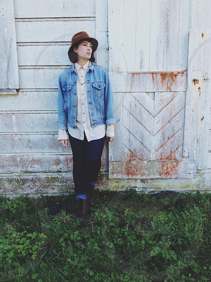 woman in chambray denim jacket white collared shirt and jeans leaning against wall in brown hat photo