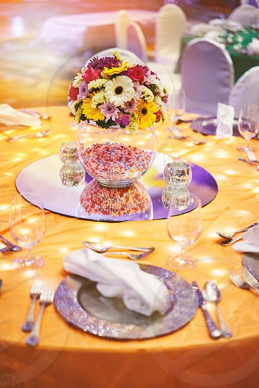 Close-up reception dinner table settings in wedding party sangeet of indian wedding with light decoration under the table with a big glass vase of flower bouquet decoration photo