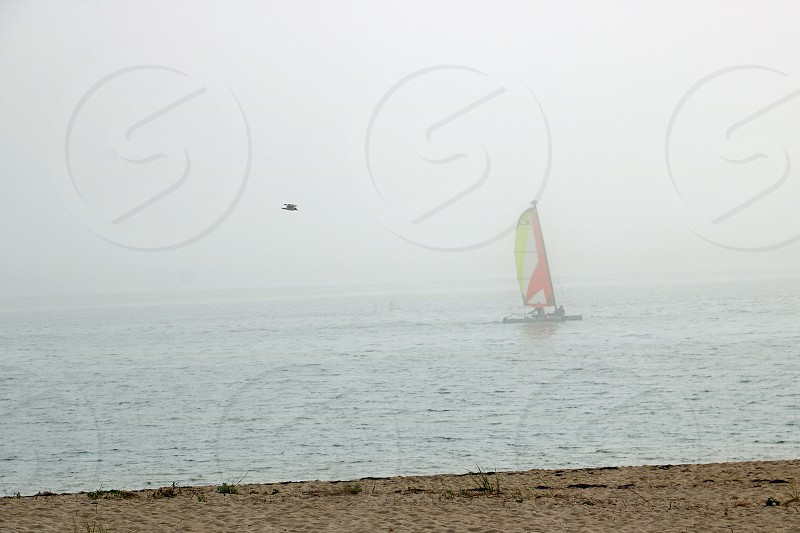 Small sailboat is seen through the morning mist on a calm ocean photo