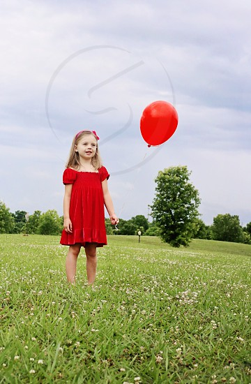 girl in red dress near red balloon photo