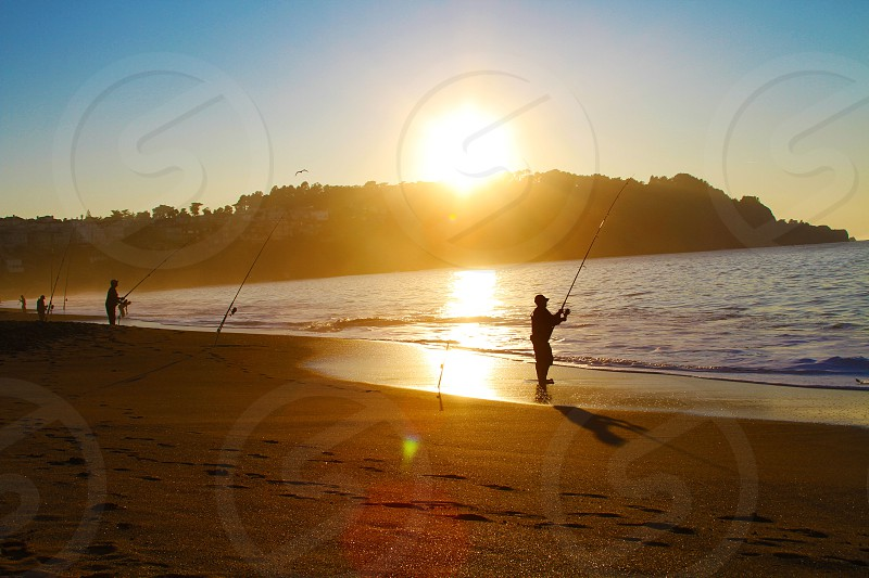 man fishing silhouette with sunset view photo
