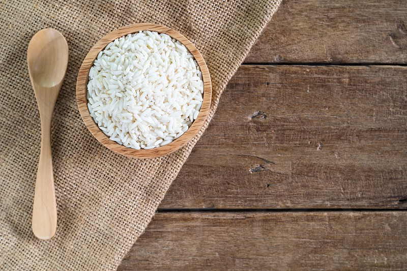 raw white sticky rice in wood bowl with wood spoon on gunny sack cloth on wooden table top view with copy space photo