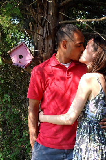 man and woman kissing under the tree photo