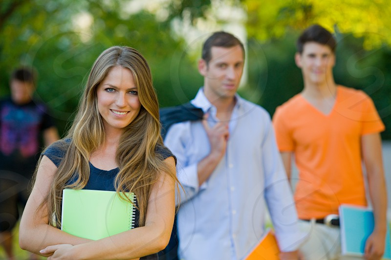 Group of college students standing on lawn of campus portrait photo