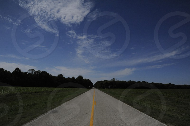 Two lane road disappearing into forested horizon photo