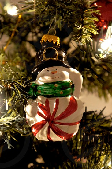 Peppermint snowman holiday ornament on a Christmas tree photo