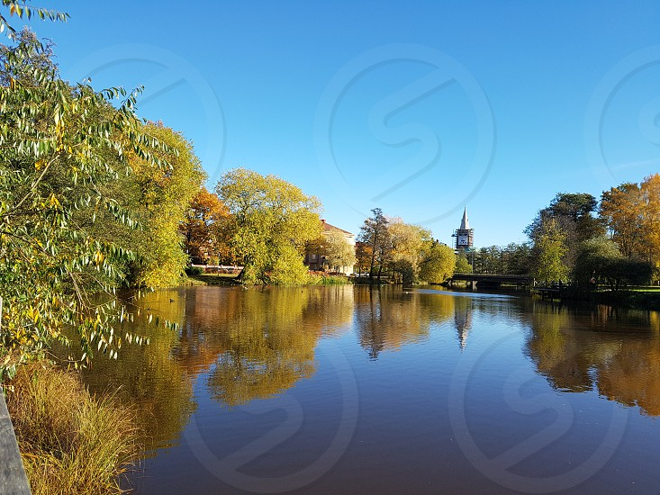 River Svartån in Örebro Sweden. A sunny sutumn day with lots of colors in the trees leaves. a foilage of green yellow and orange. Blue sky and water reflections. photo