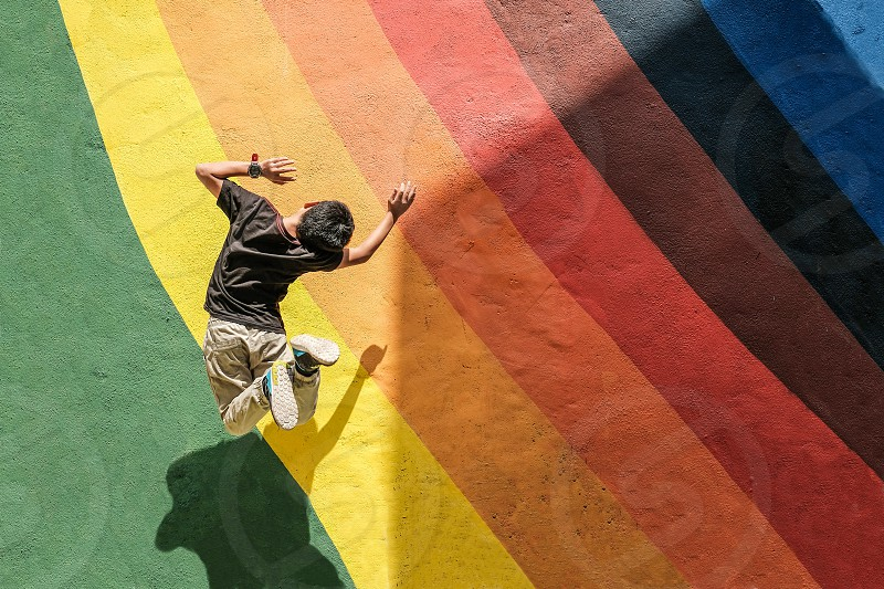 A boy jumping against colorful wall photo
