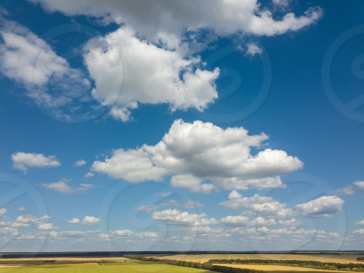 Aerial bird's eye view from drone to a rural landscape with farmlands on a background blue cloudy sky in a sunny day. Natural cloudscape. photo