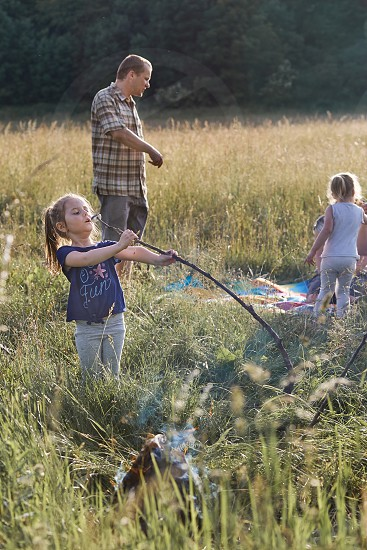 Little girl eating a marshmallow after roasting it over a campfire on a meadow. Candid people real moments authentic situations photo