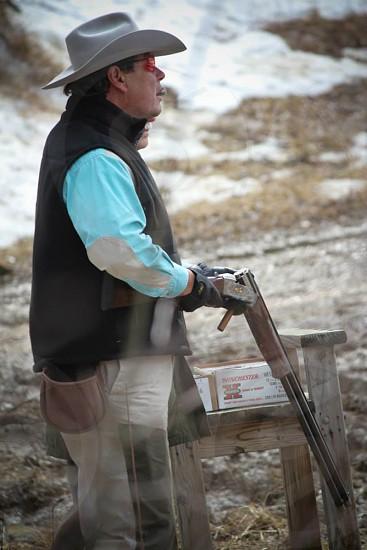 man in gray cowboy hat and black vest holding gray gun photo
