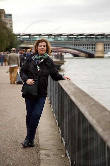 woman in black jacket leaning on metal railings photo