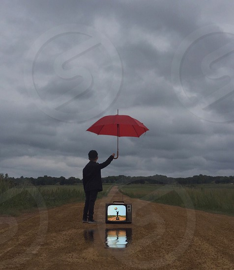 boy standing in the middle of a brown dirt road  holding a red umbrella over a black crt tv photo