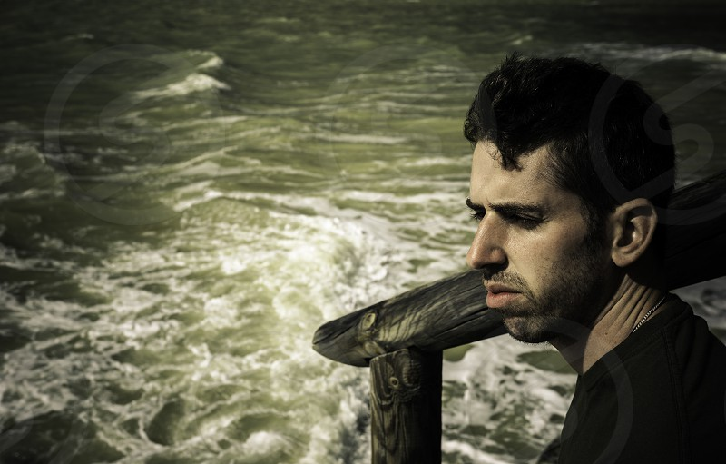 Young man sitting near the sea photo