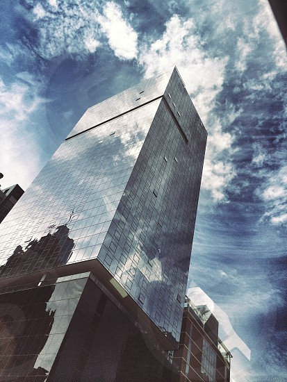 low angle photography of glass high-rise building under white clouds photo