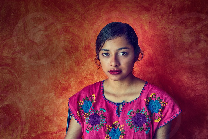 Mexican woman with mayan dress latin ethnicity on orange background photo