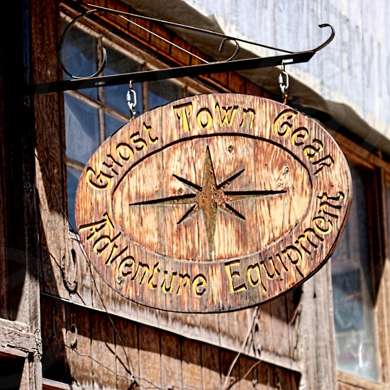 Colorful vintage western sign hangs in Jerome Arizona photo