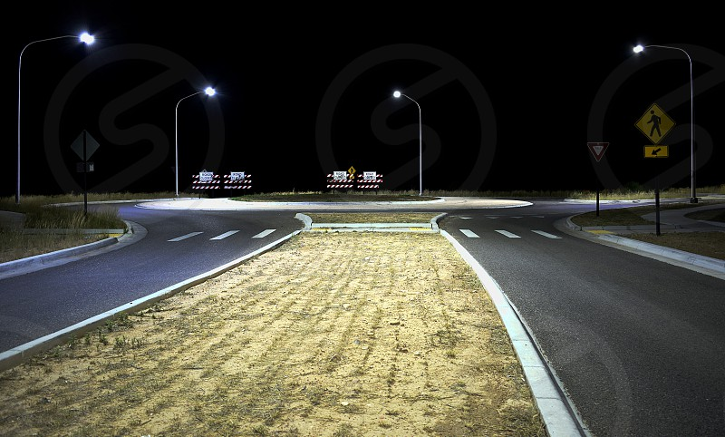 Nightscape of deserted traffic roundabout illuminated by streetlight. photo