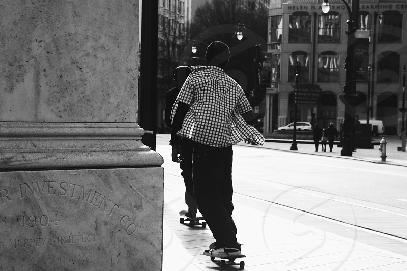 man in white and black checked button up shirt and black pants skateboarding on road photo