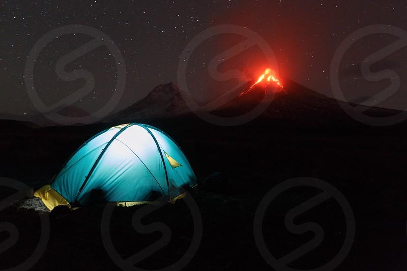 Volcanic landscape of Kamchatka: night view of illuminated tourist tent on background eruption Klyuchevskoy Volcano. Eurasia Russia Far East Kamchatka Peninsula Klyuchevskaya Group of Volcanoes. photo