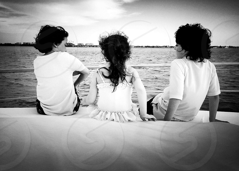 grayscale photography of girl sitting in between of two boys photo