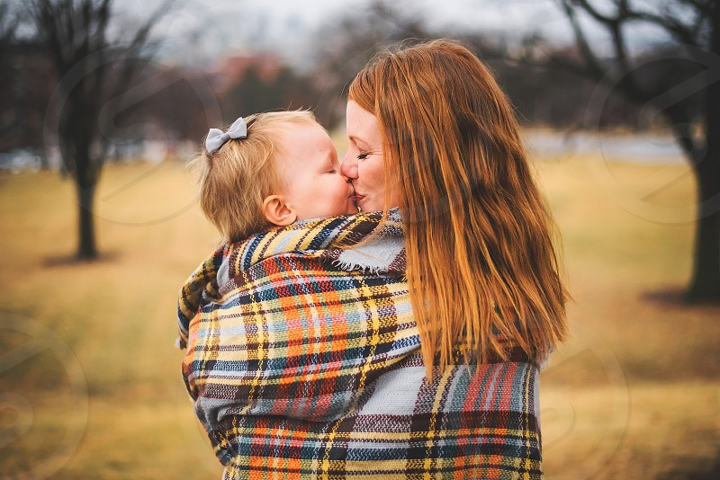 mom and daughter kissing in plaid blanket photo