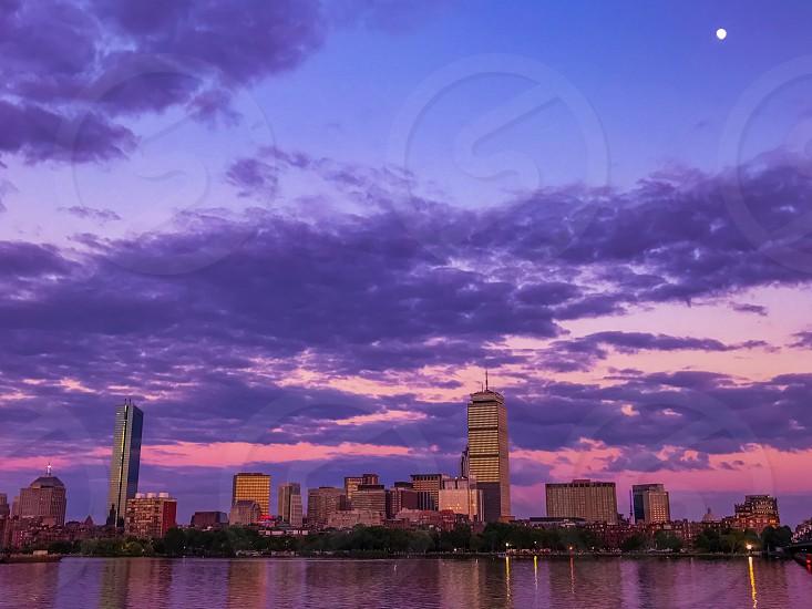Bostontwilightriversunsetcitywatermoonskyskylinepurplevioletnightskyscraperbuildingclouds photo