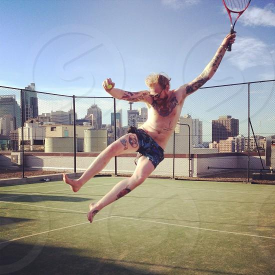 man jumping while holding racket  photo