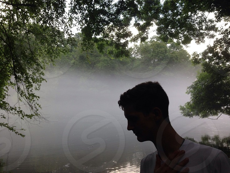 Silhouette in front of foggy river photo