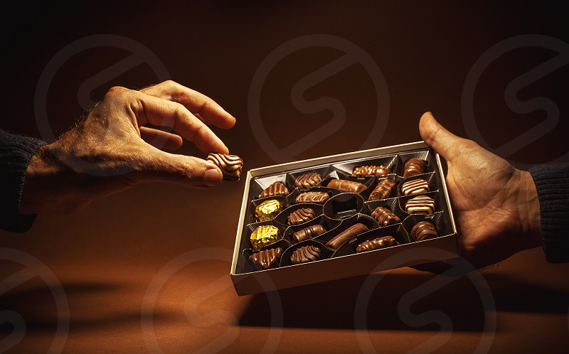 Male hands are holding an open box of chocolates and pick one.  photo
