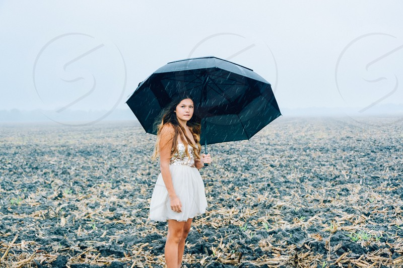 A young woman sheltering herself from the rain. photo