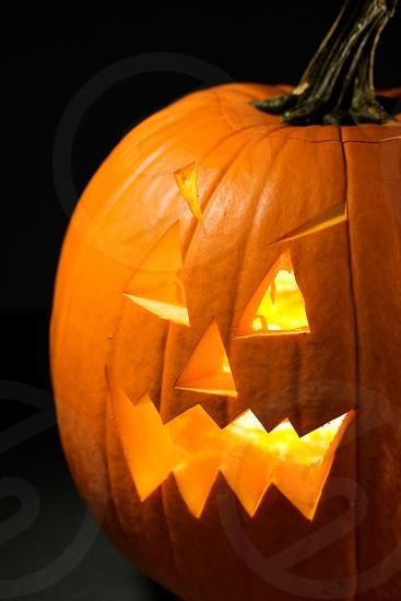 Spooky Halloween Jack O Lantern.  pumpkin halloween holiday glowing lit jack o lantern carved orange  photo