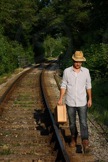 A man holding a suitcase and wearing a straw hat walks along train tracks photo