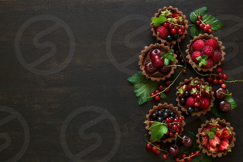 Close up of chocolate tartlets with chocolate cream fresh strawberries raspberries blueberries red currants and cherries on black wooden background. Selective focus photo