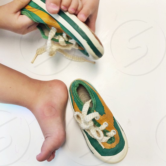 Toddler putting on shoes photo