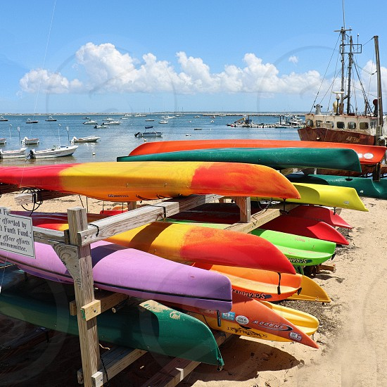 Colorful kayaks are stacked on a beach photo