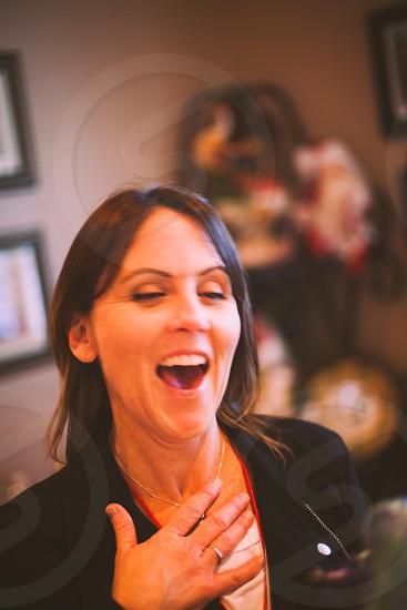 laughing woman in black jacket touching her chest photo
