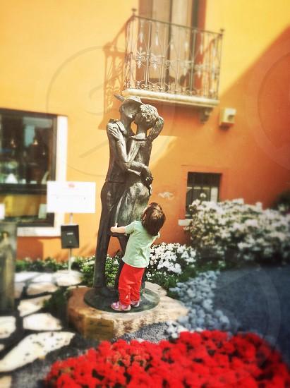 man and woman kissing statue macro photography photo