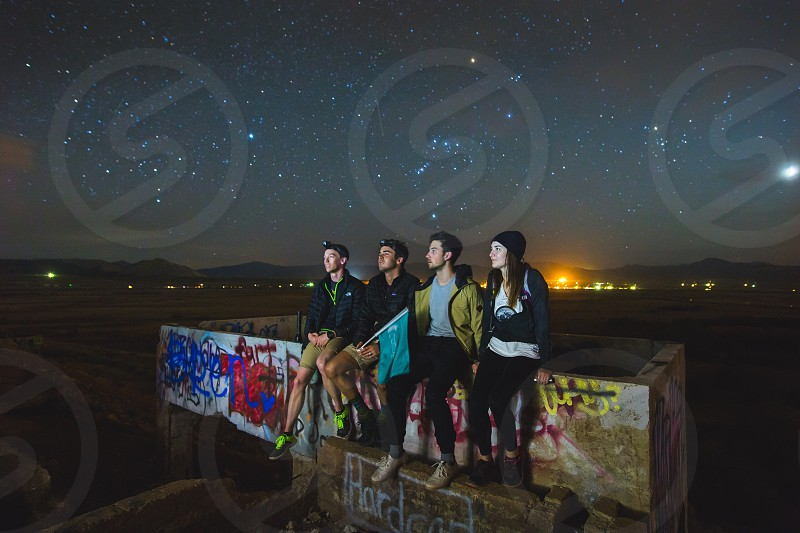 4 people sitting on graffiti painted concrete wall in middle of plains during night time photo