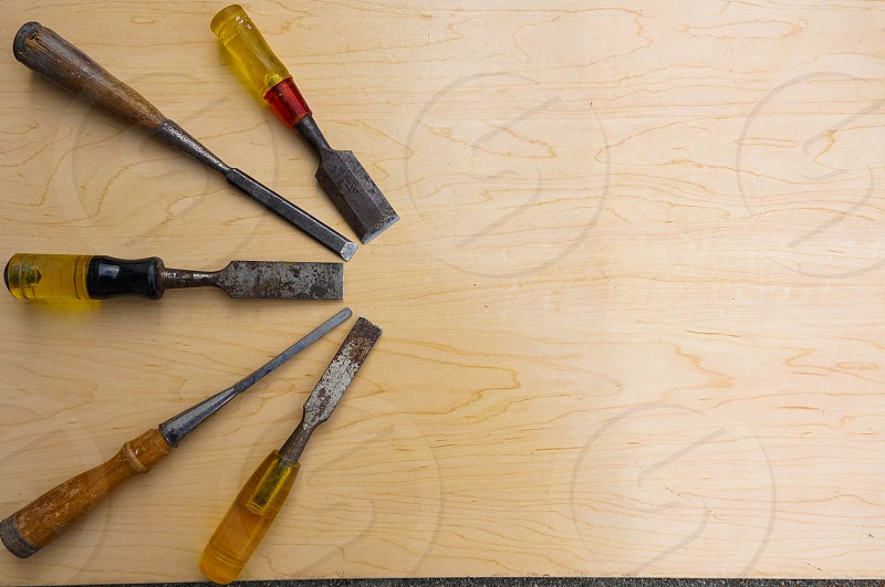 Antique chisels against a wooden background reflect concepts of skill craftsmanship and precision photo
