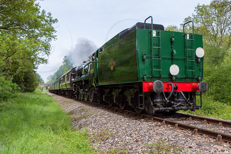 KINGSCOTE SUSSEX/UK - MAY 23 : Rebuilt Bulleid Light Pacific No. 34059 steam locomotive near Kingscote Station on May 23 2009. Three unidentified people. photo
