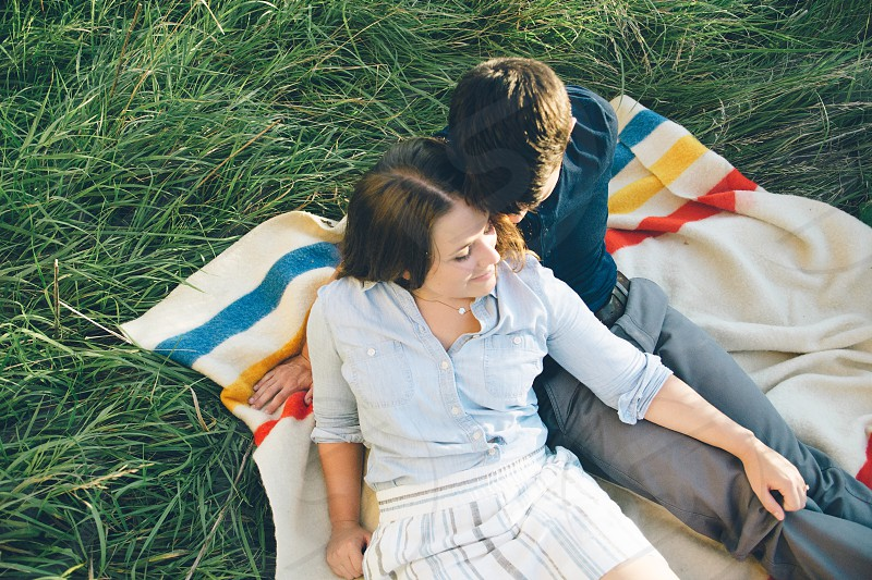 couple sitting side by side on picnic blanket photo