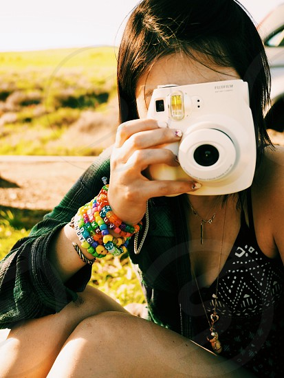 woman wearing rainbow beaded bracelets holding up a white camera to take a picture photo