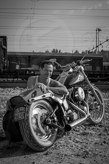 grayscale photo of man in tank top squatting beside parked motorcycle photo