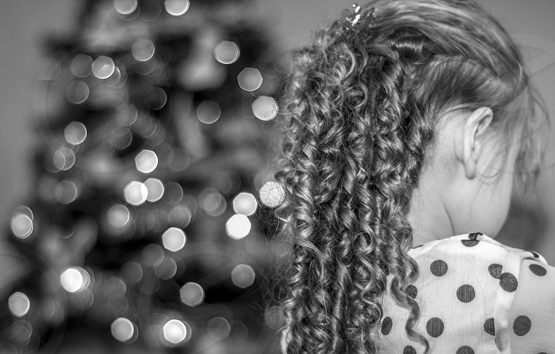 Christmas xmas festive tree lights bokeh young girl infront looking towards decorations decoration hair style  photo